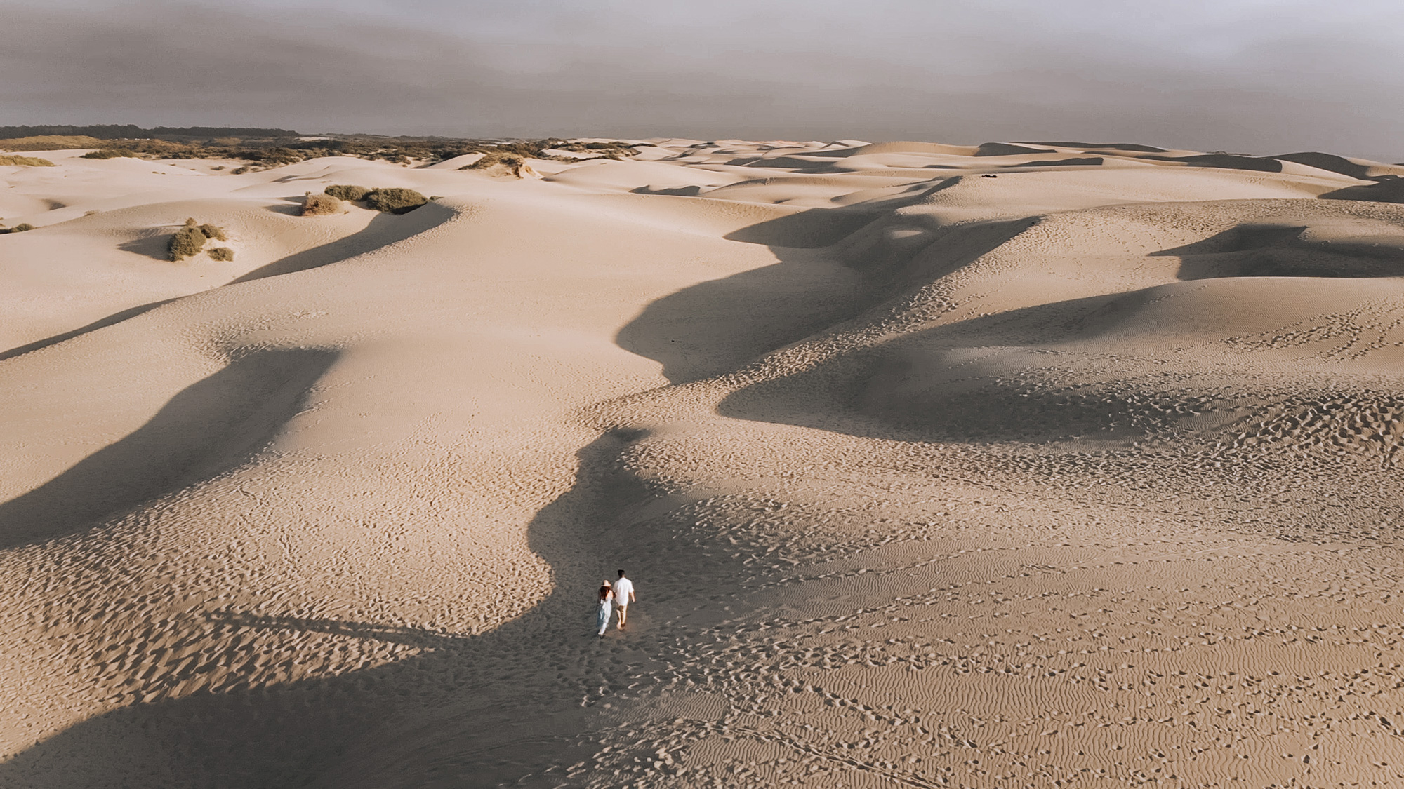 Drone shot of an engaged couple walking up sand dunes in Oceano Dunes, CA