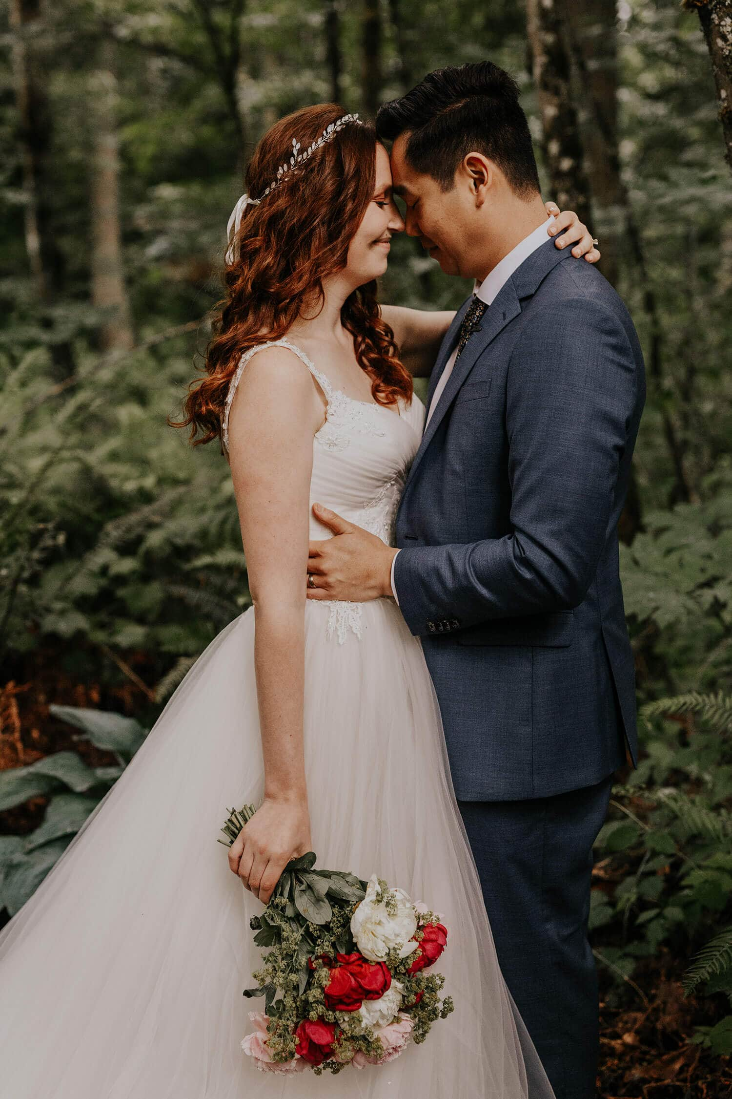 Romantic shot of the bride holding her bouquet, and groom holding her in his arms on a backyard of their house