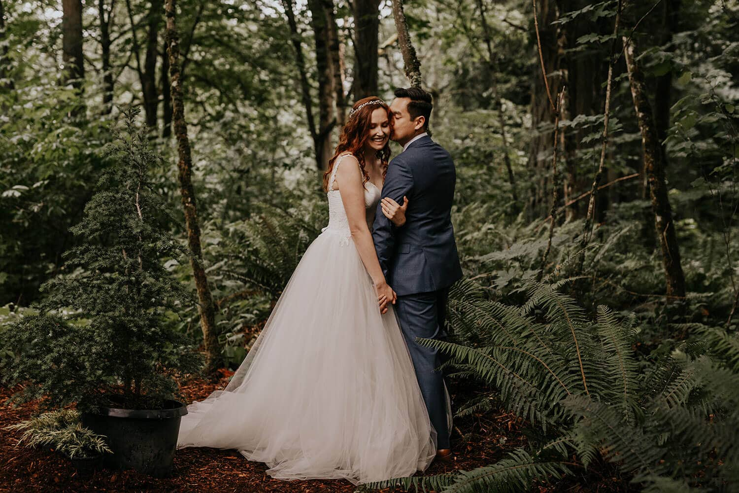 Lovely bride and groom standing in a beautiful wedding gowns in a lush forest in Seattle