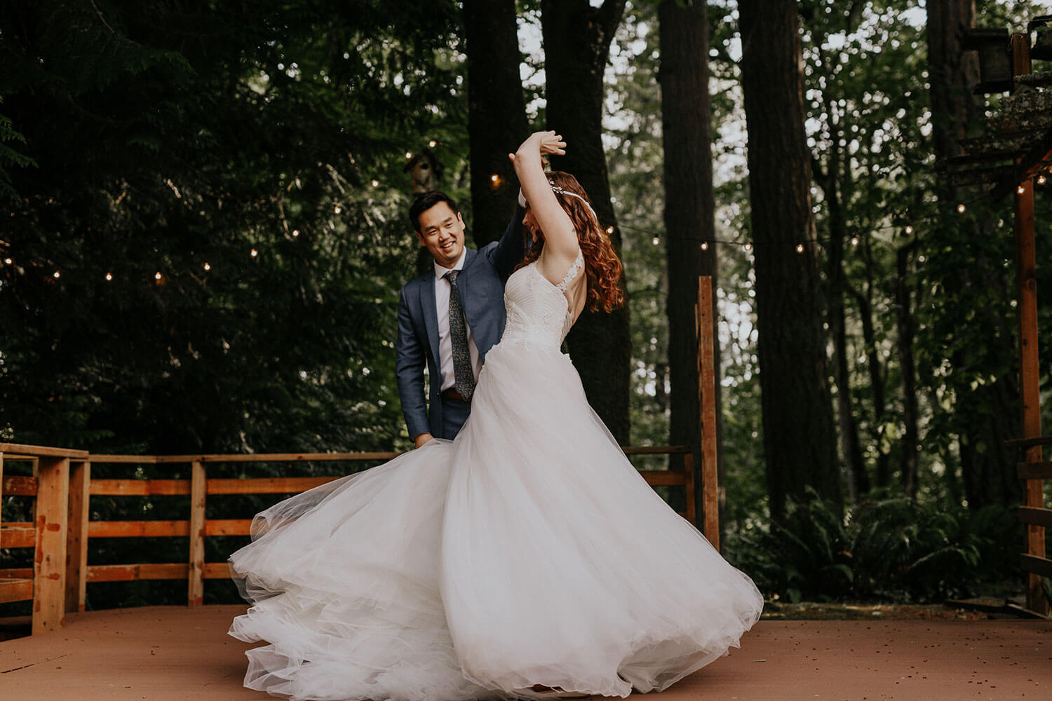 Bride in a gorgeous wedding dress and groom dancing at home for the first time on a backyard
