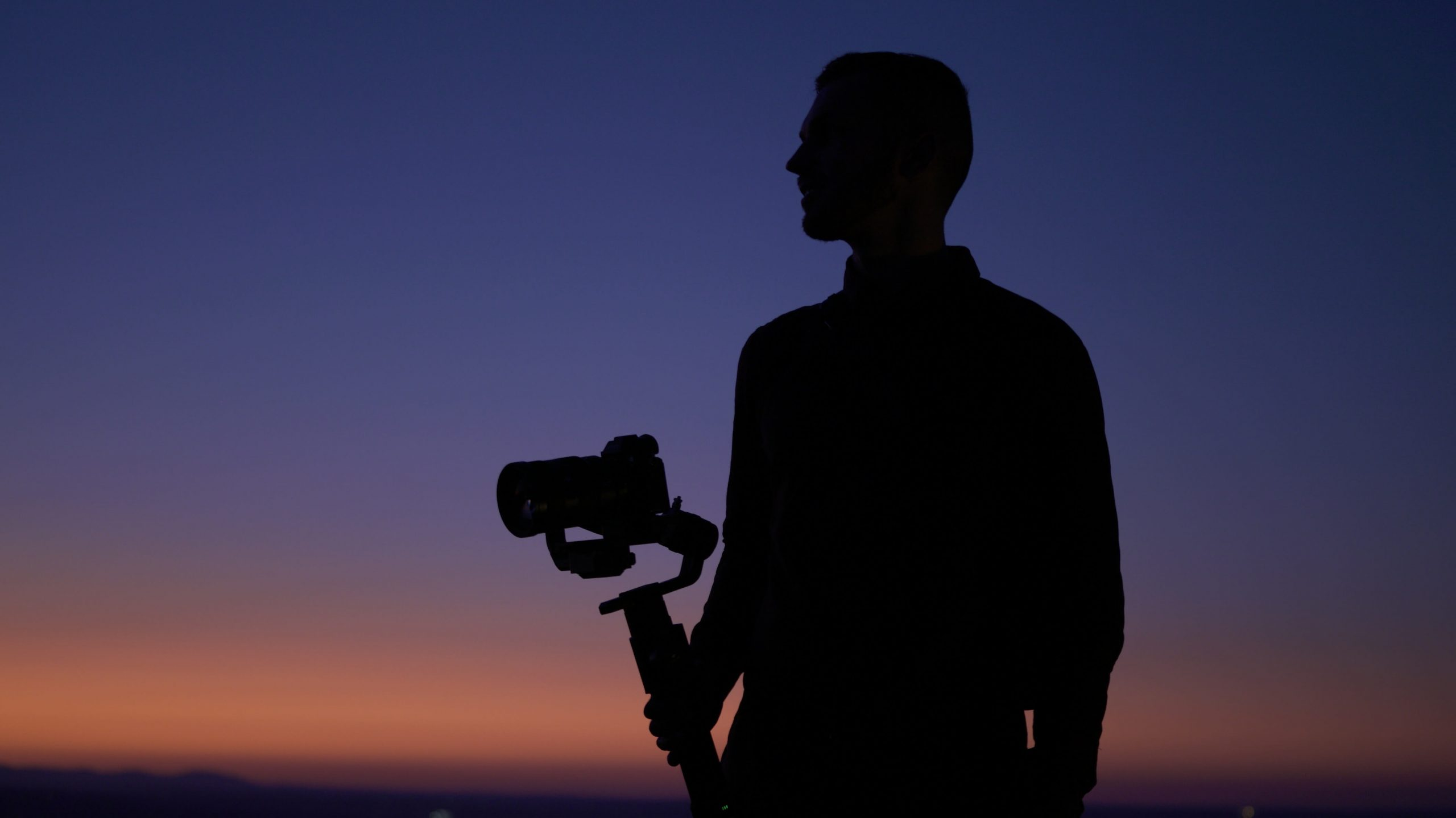 Videographer with gimbal on a sunset time