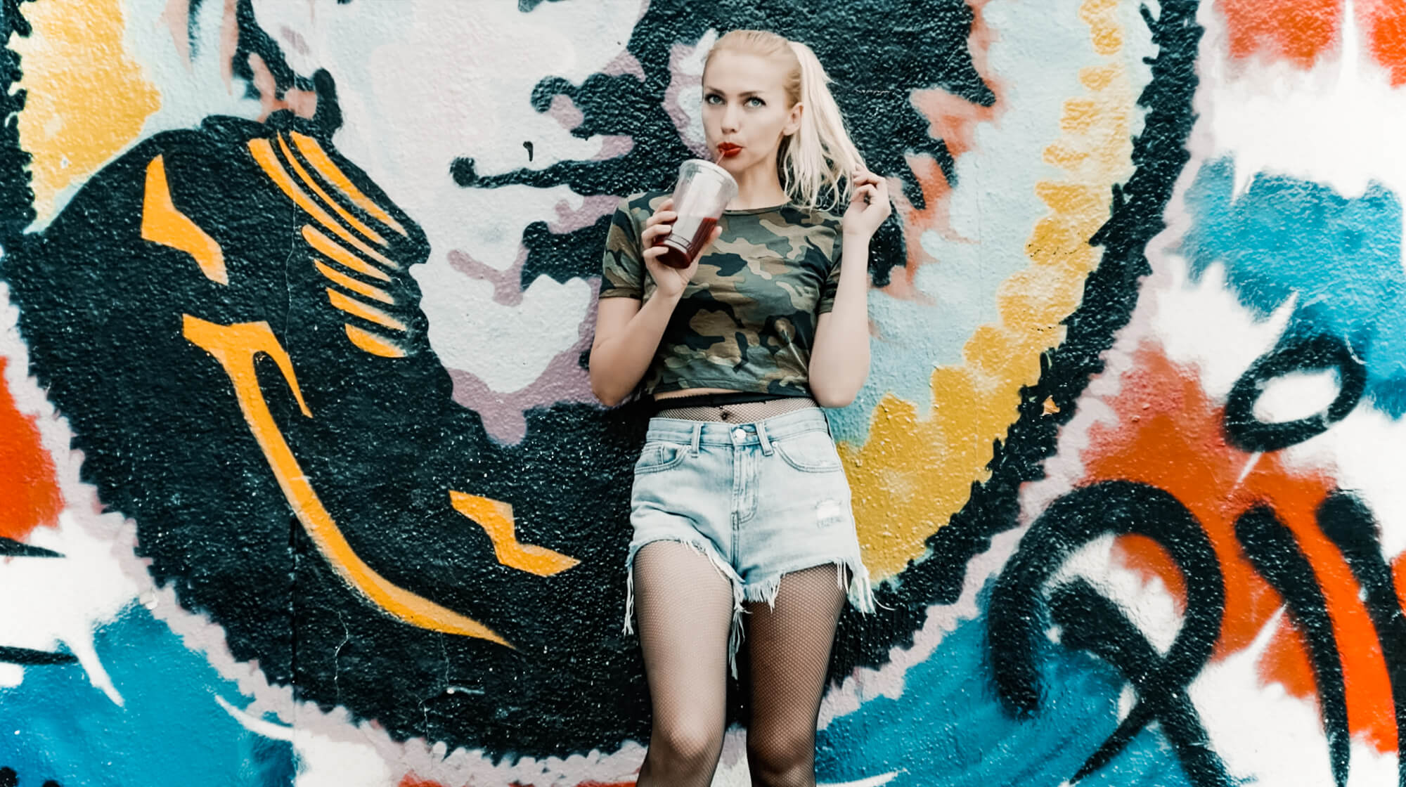 Pre-wedding shoot outfit ideas. Girl with a drink standing by the graffiti wall on a street