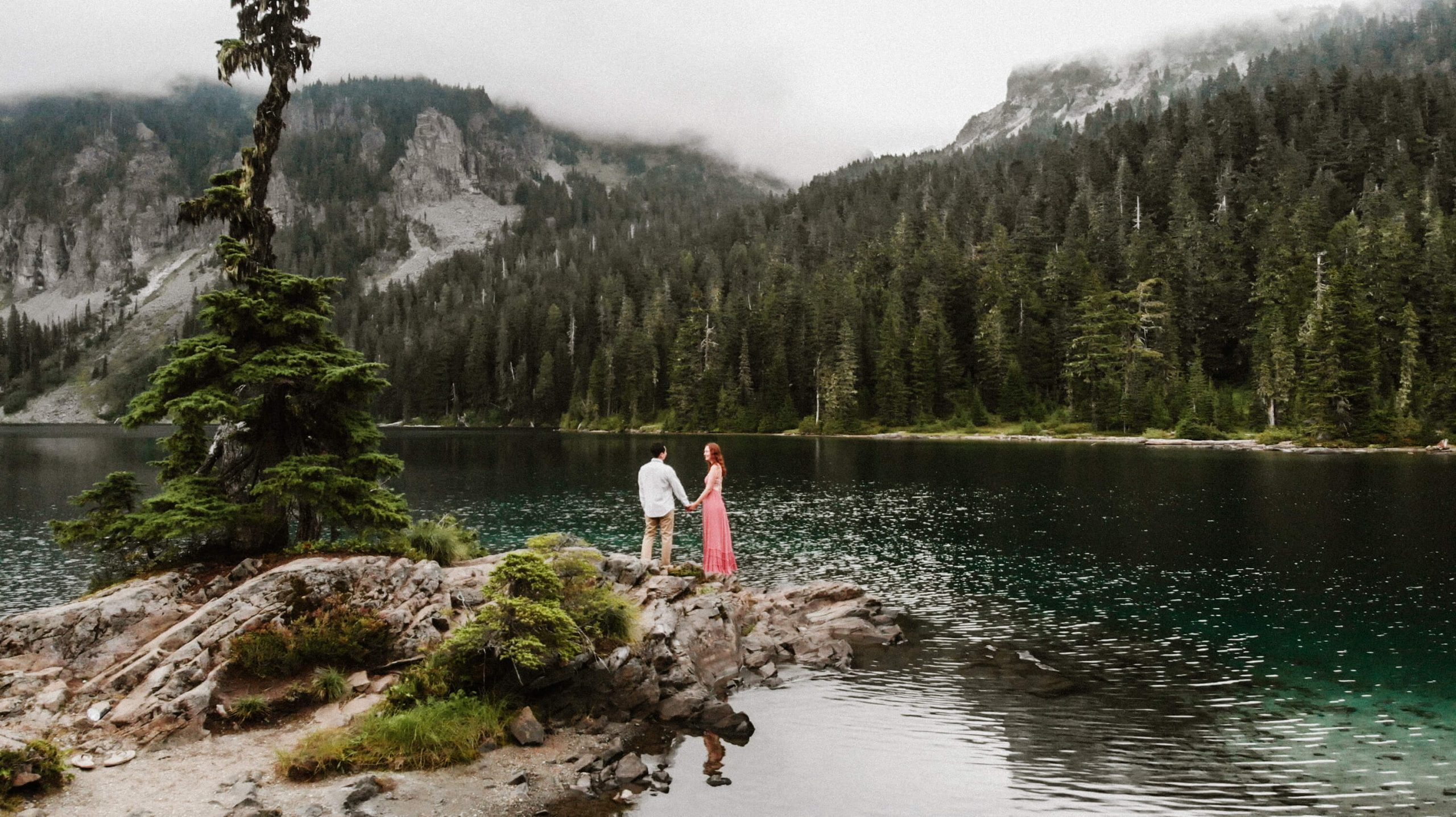 Couple standing on the edge of rocks in Mowich Lake, WA