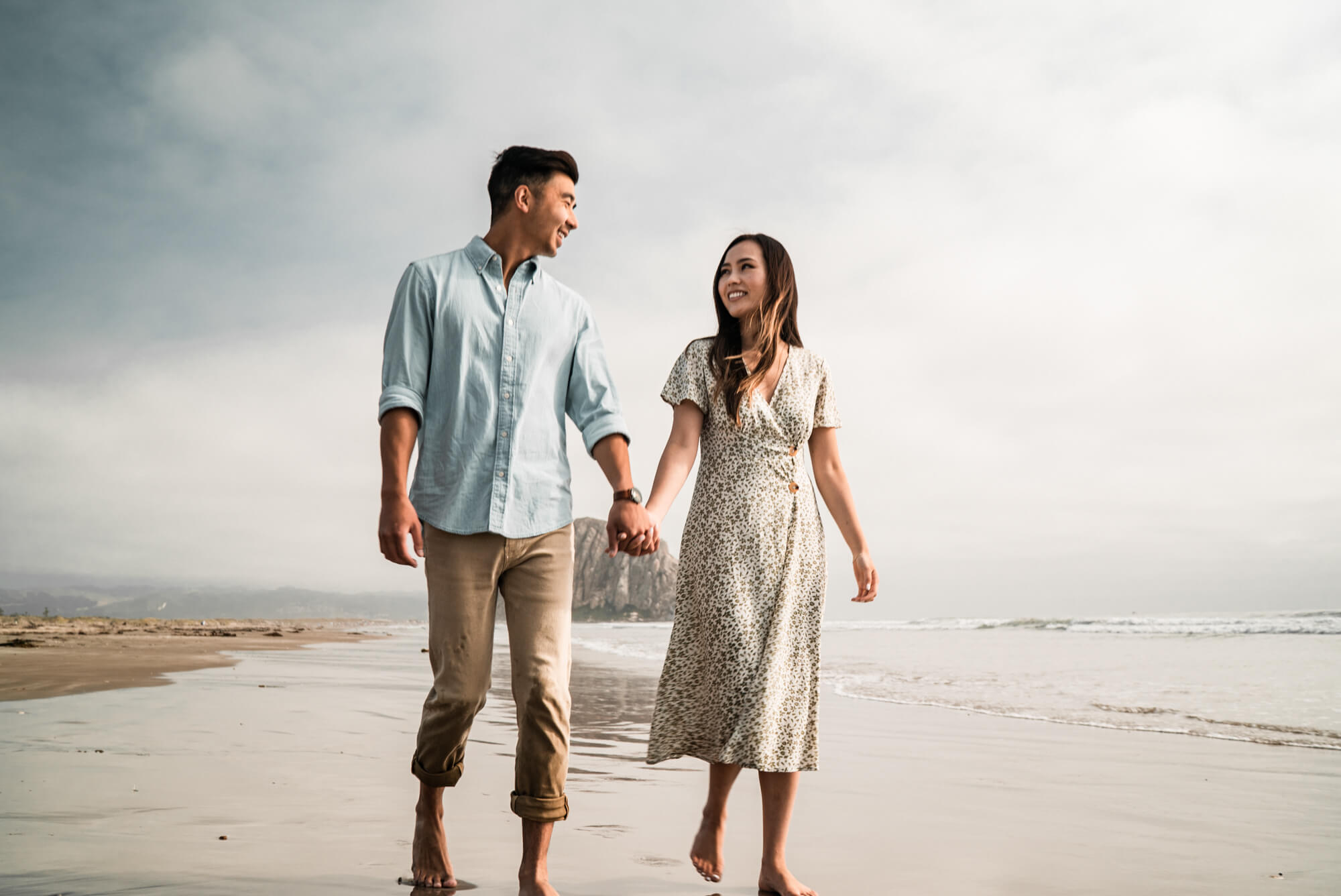 lovely asian couple walking on the beach