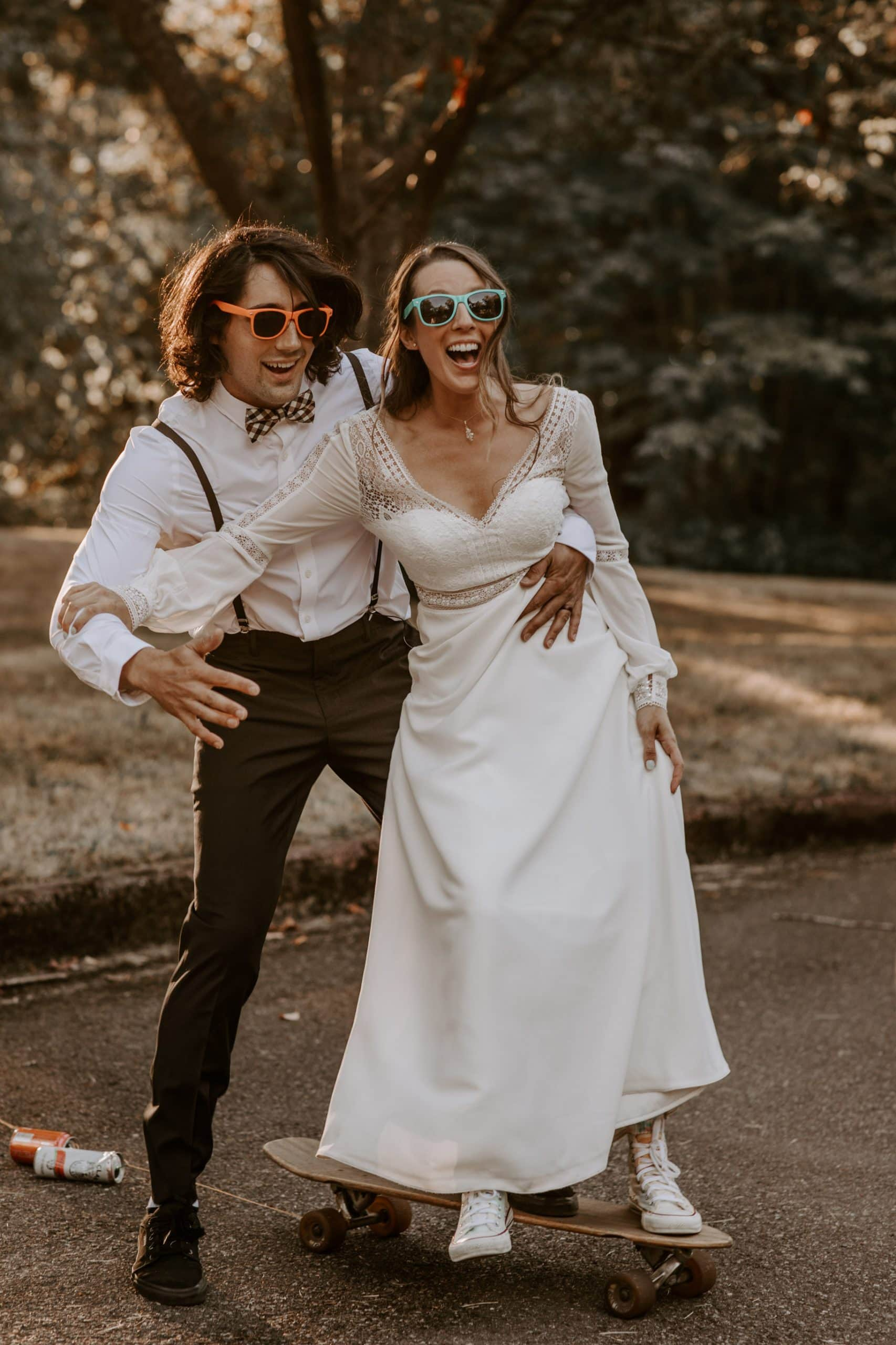 Bride and groom wearing colorful glasses and riding a skateboard after the wedding ceremony in Seward park in Seattle