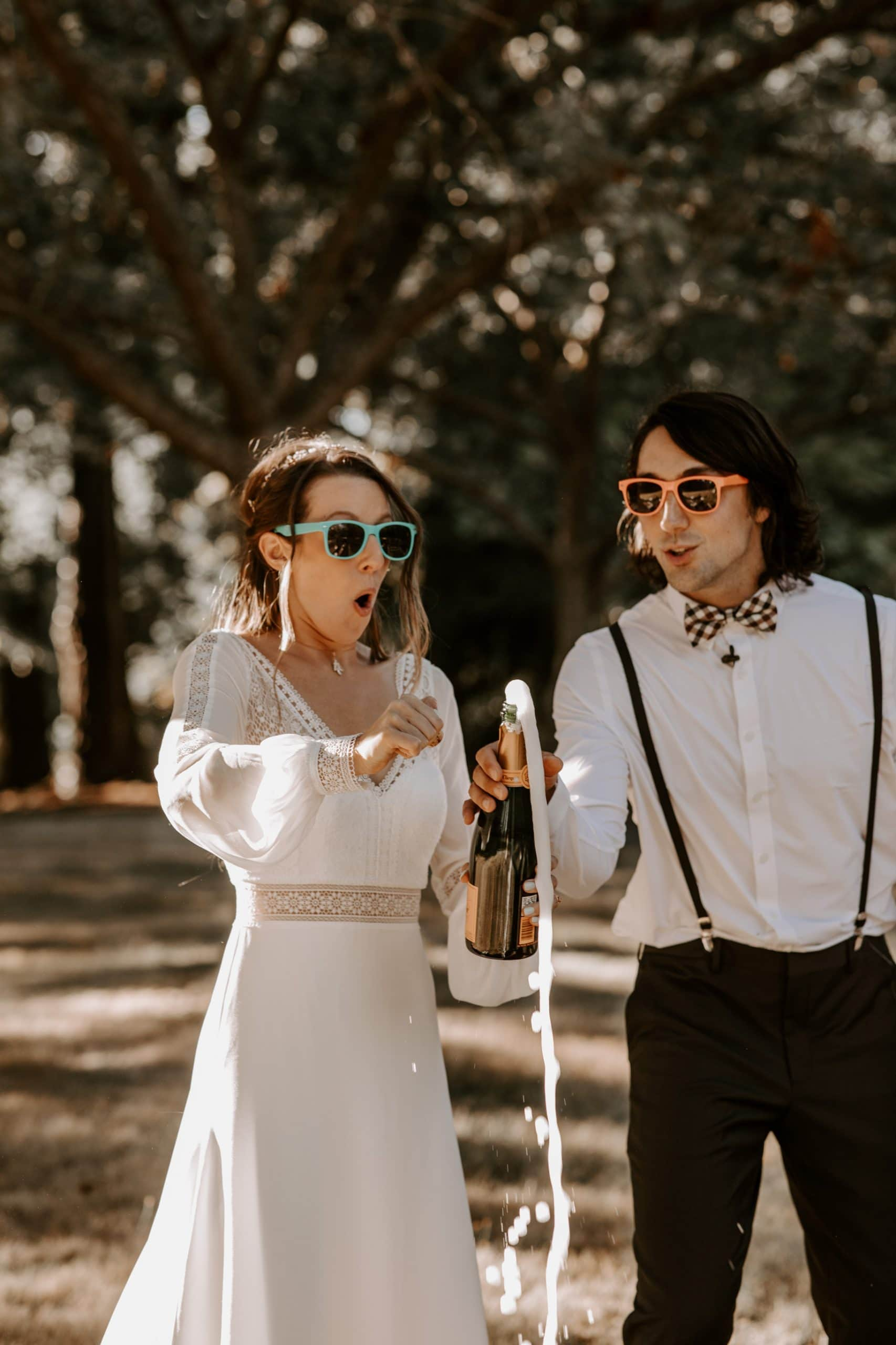 Bride and groom popping champagne in Seward Park, Seattle