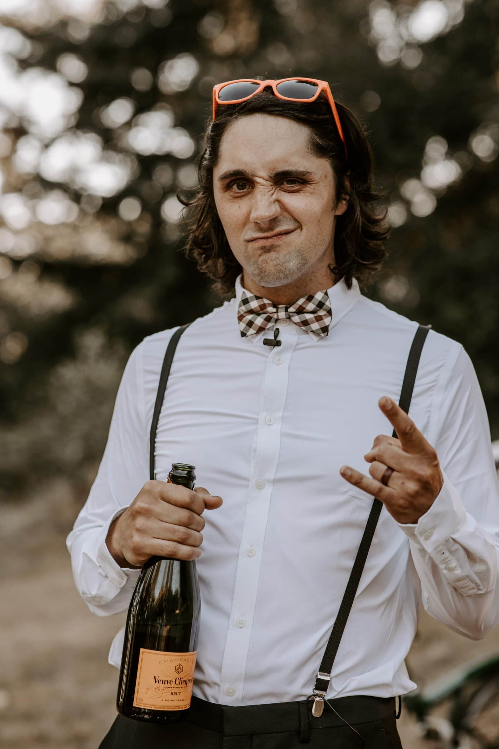 Groom holding champagne bottle and showing the rock-n-roll sign
