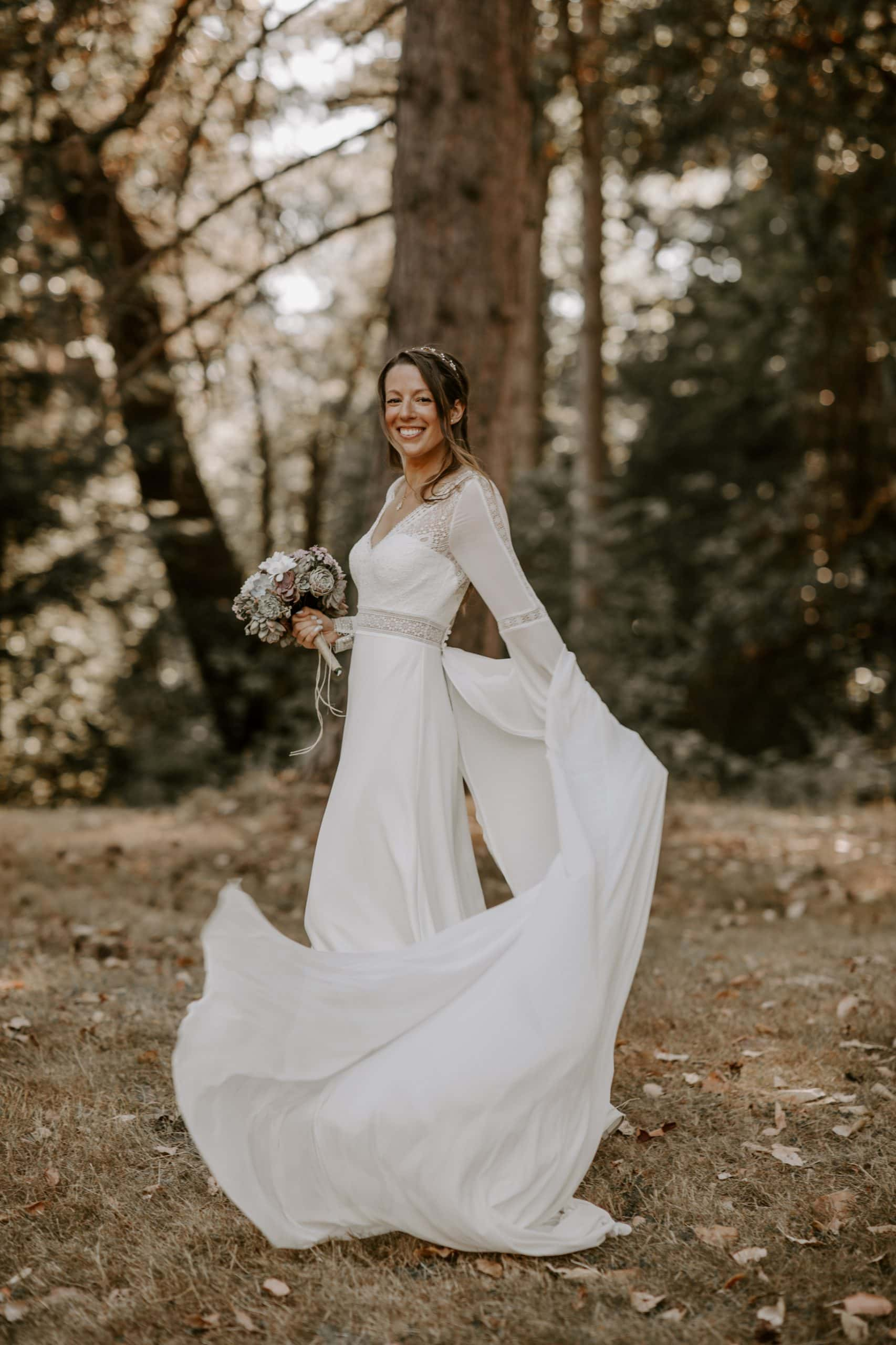 Smiling bride waving her beautiful wedding dress in a forest in Seward Park, Seattle